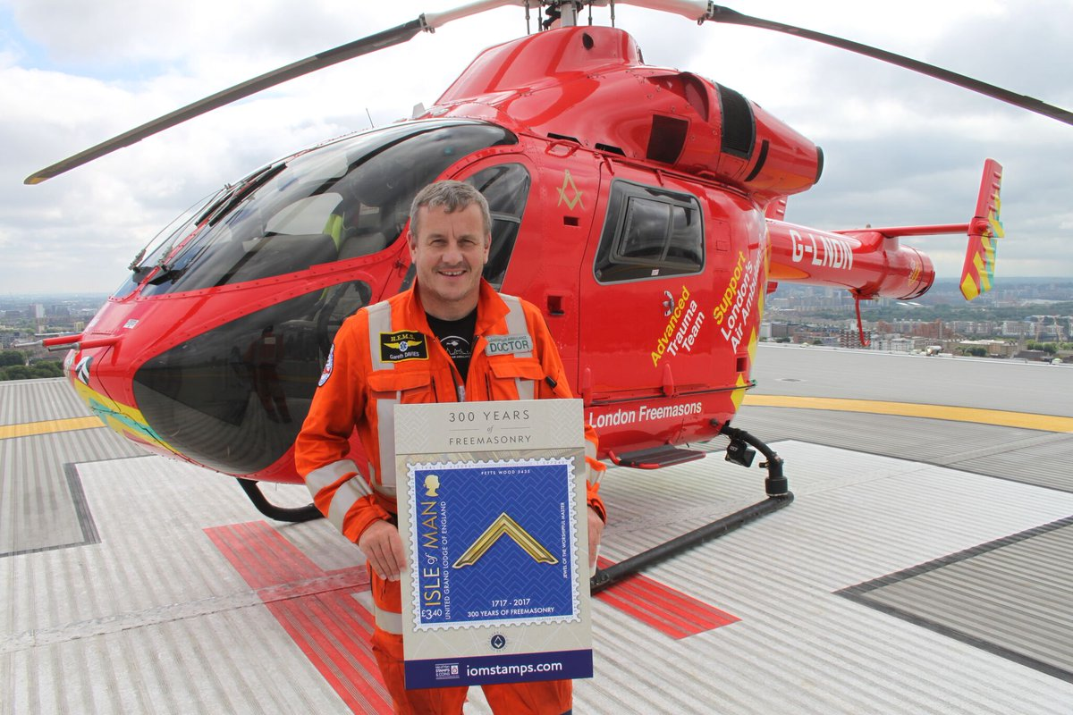 Pictured here is Manxman and Medical Director of London's Air Ambulance, Dr Gareth Davies, on the landing pad at the Royal London Hospital, after being presented with a blow-up of the stamp and a donation of £1500 from Barbican Lodge, which is featured on one of the stamps.