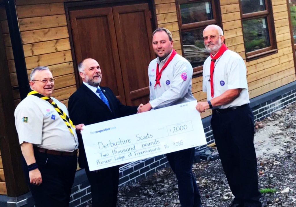 Photo of Master of Pioneer Lodge, W Bro. Andy Brown, accompanied by the Charity Steward, W Bro. Don Newing, and W Bro. Tony Harvey, presented the County Commissioner for Derbyshire, James Stafford, accompanied by the centre's project manager, Tom Stoddart, with the cheque for £2,000.