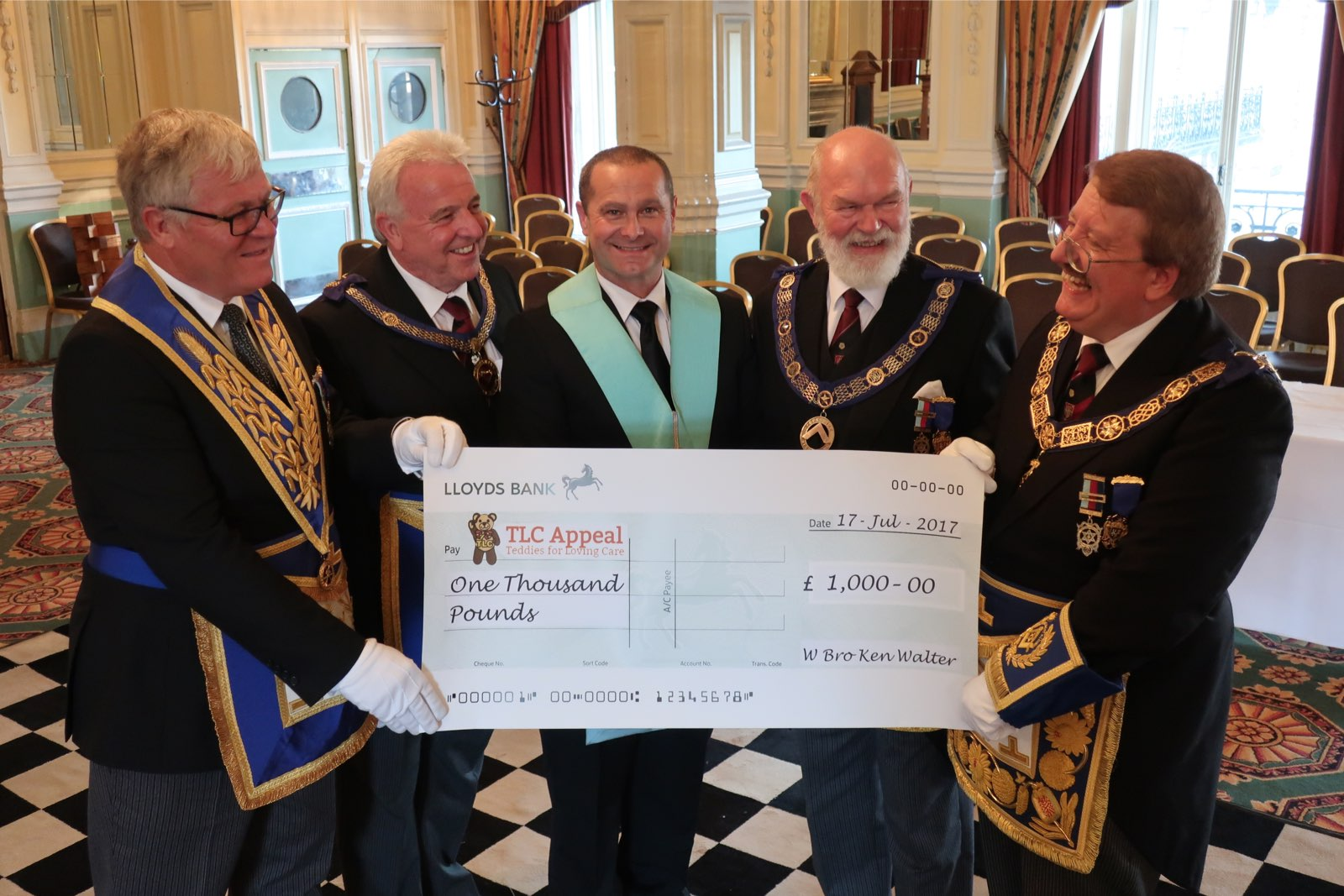 Photo (from L to R) W Bro John Watson (Charity Steward), W Bro Roger Newhouse (APGM), W Bro John Eaton (stand-in Master for the visit), VW Bro Stuart Grantham (DPGM) & RW Bro David Pratt (PGM) with the cheque for £1,000 to TLC